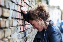 01 Feb 2015, Potsdam, Germany --- Profile of woman with curly brown hair leaning head against brick wall --- Image by © Annie Hall/Westend61/Corbis